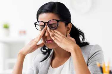 Göz kapağı seğirmesi ile başa çıkmak için gözlerini ovuşturan kadın.