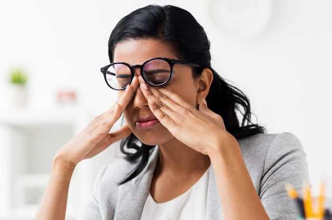 Frau reibt sich die Augen, um mit zuckenden Augenlidern fertig zu werden.