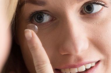 Woman placing contact lens on to eye