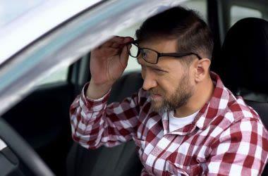 Short-sighted man looking at dash of car