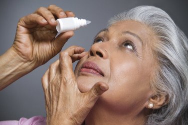 An older Indian woman putting eye drops in her eye.