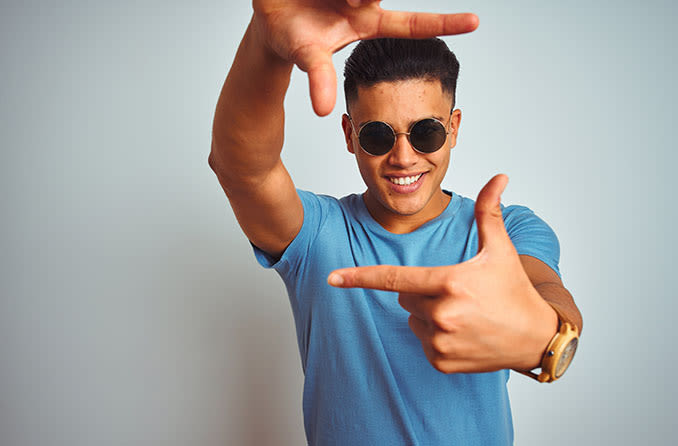 man wearing sunglasses with his fingers extended out to frame his face