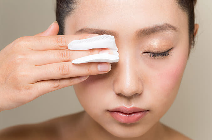 woman cleaning and treating her swollen eyelid