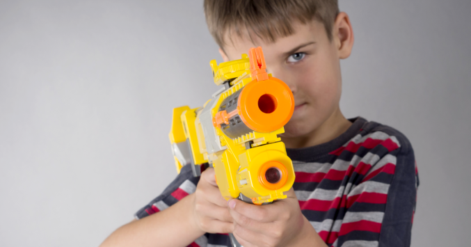 boy with toy dart gun
