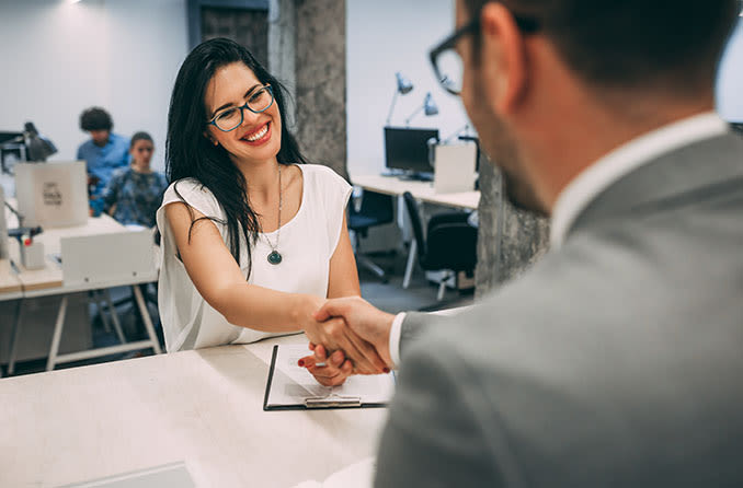 Man and woman wearing eyeglasses and shaking hands in an office setting