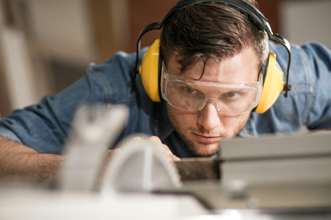 Man cutting wood wearing safety glasses
