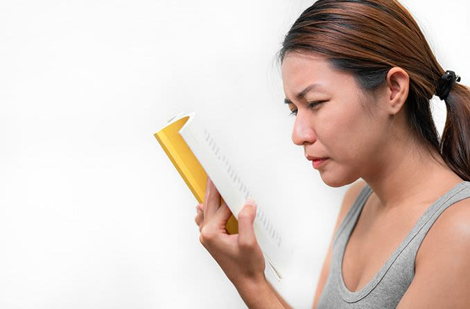 Asian woman squinting to read book up close