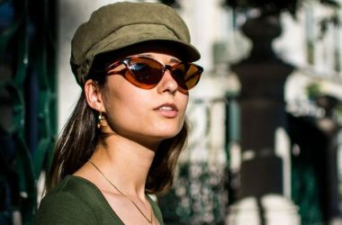 Woman wearing green hat and non-prescription sunglasses.