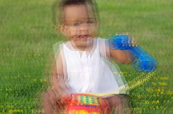 Simulazione di qualcuno con visione doppia (diplopia) che vede un bambino che gioca nell'erba.