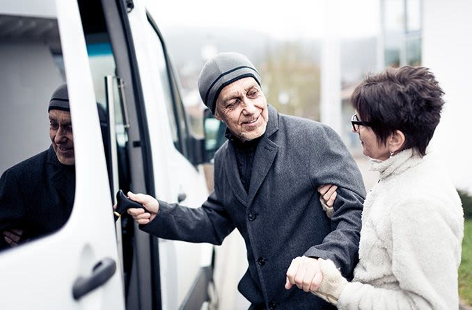 Woman helping an older man into a van
