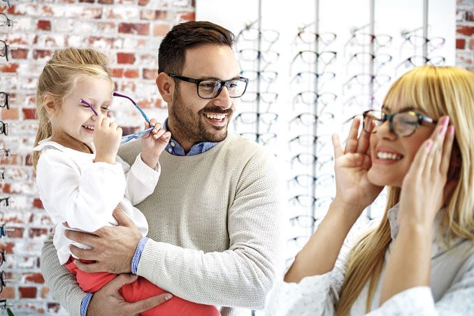 Family trying on glasses in store