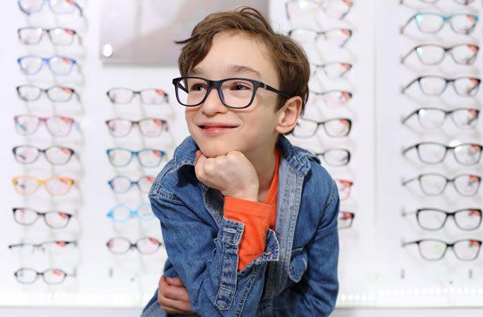 Glücklicher Junge posiert mit seiner neuen Brille