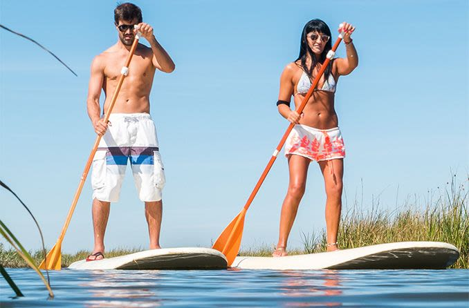 Couple wearing sunglasses while stand up paddle boarding