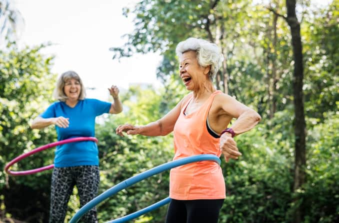 mature women exercising with hula hoops