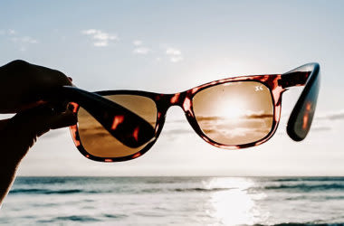 Hand holding sunglasses in front of sun at beach