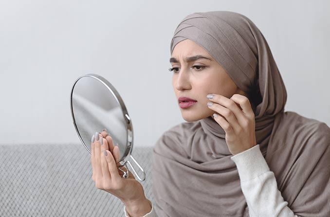 امرأة تنظر إلى عينيها في المرآة في دهشة