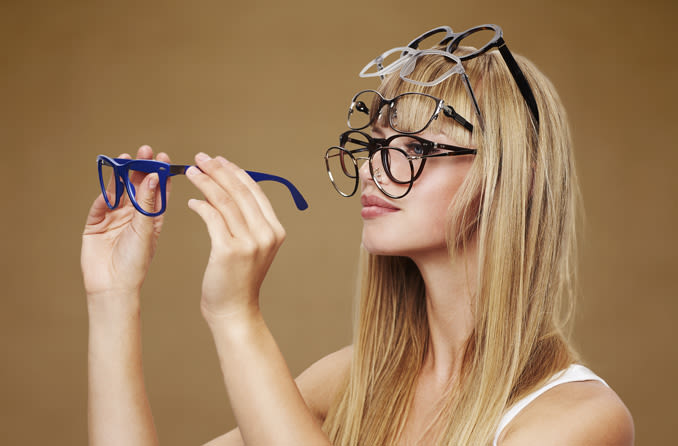 Woman wearing multiple eye glasses on her head and face
