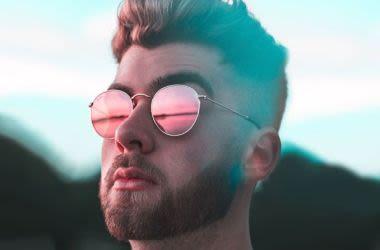 man wearing prescription sunnies stares at sunset