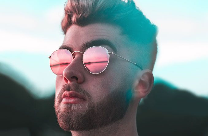 man wearing prescription sunglasses stares at sunset