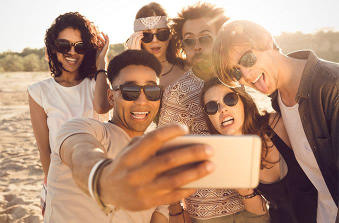 young group of people wearing sunglasses on the beach taking a selfie