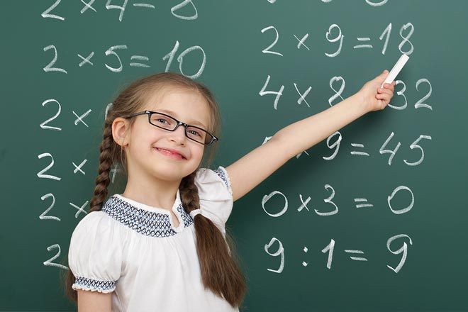 Girl pointing at a chalk board