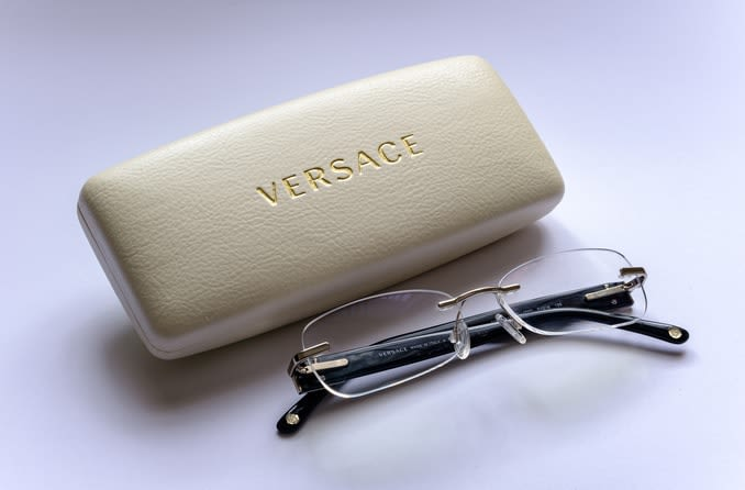 A pair of classic rimless Versace glasses displayed with ivory glasses case