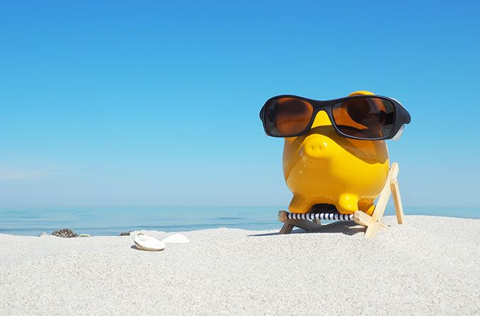 piggy bank wearing sunglasses on the beach