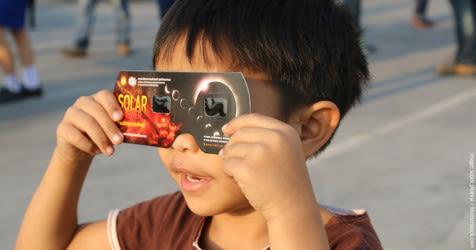Niño pequeño que mira a través de los vidrios del eclipse que miran para arriba un eclipse solar.
