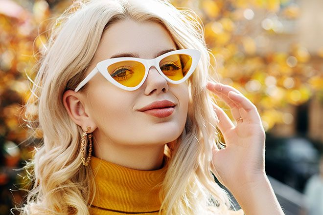 Woman wearing yellow lenses and white framed cat-eye sunglasses outdoors in autumn