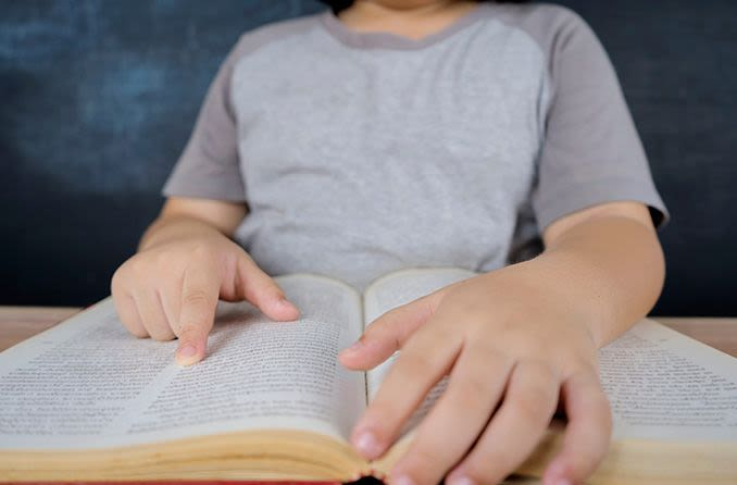 young child reading a book using finger to mark words