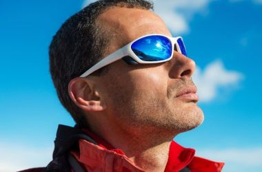 Man staring into sun wearing perfomance sunglasses.