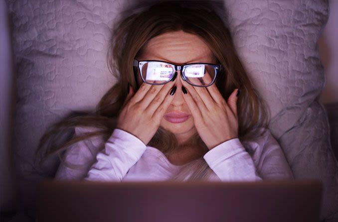 Mulher esfregando os olhos pelo uso prolongado do computador