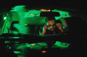 man driving at night putting on eyeglasses