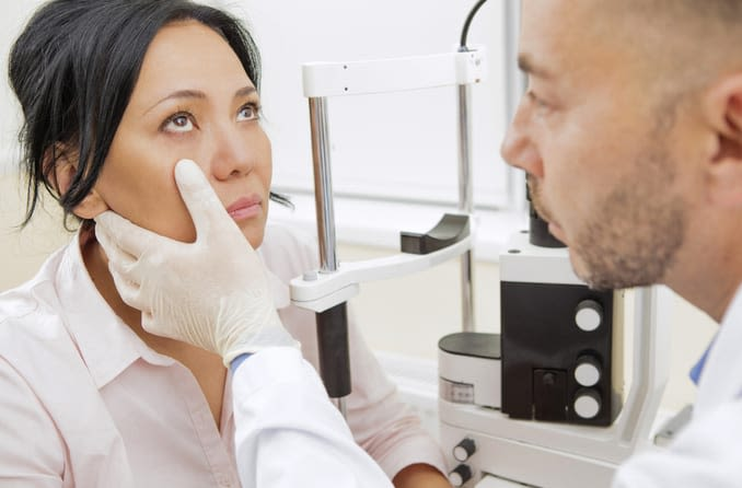 A dark-haired woman calmly looks toward the ceiling so her optometrist can examine her eyes.