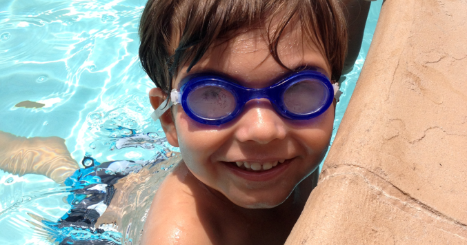 child wearing swim goggles in pool