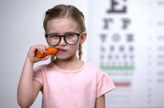 young girl eating carrots and wearing eyeglasses