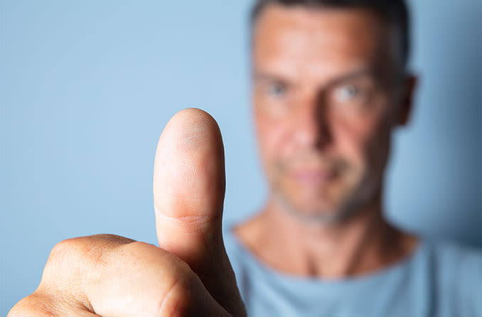 man holding thumb out focusing on astigmatism eye exercises