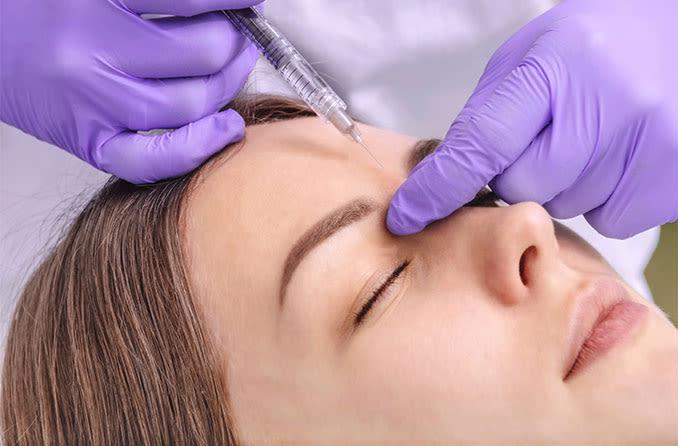 woman getting botox injections near eyelids