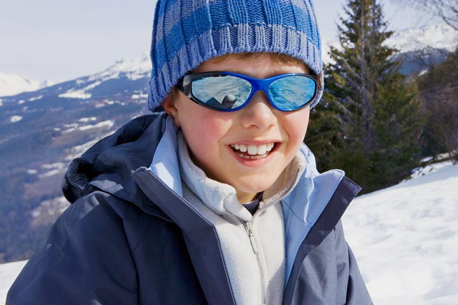 Boy wearing sunglasses on a snowy mountain