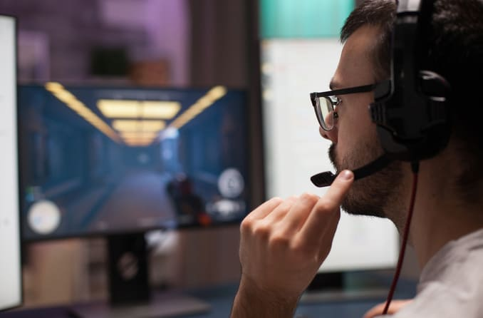 Man wearing eyeglasses and a headset while playing a video game