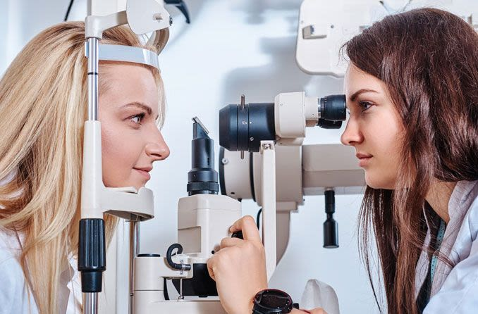 Женщина, проводящая обследование глаз у другой женщины Zhenshchina, provodyashchaya obsledovaniye glaz u drugoy zhenshchiny