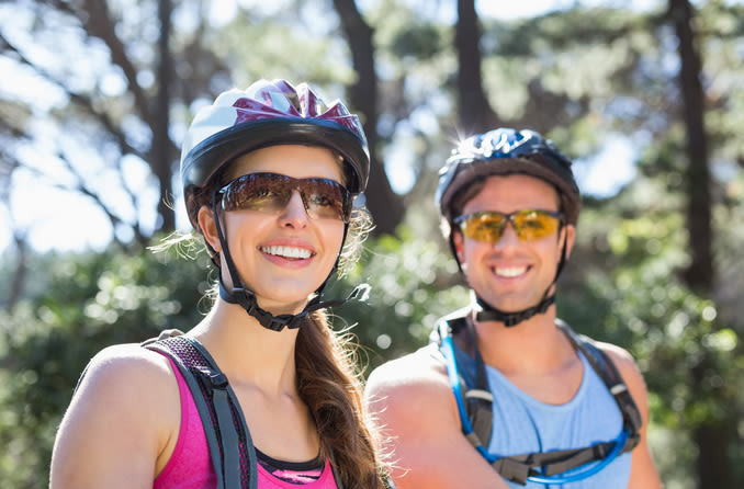 Male and female cyclists wearing wraparound sunglasses