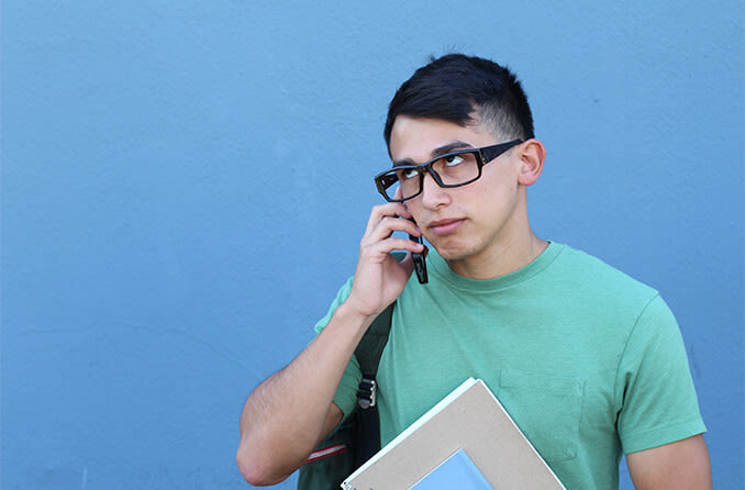 man rolling his eyes while talking on the phone