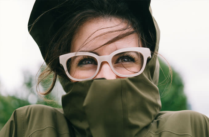 woman wearing eyeglasses looking chilly outdoors