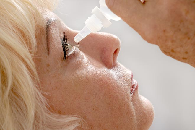 Woman applying eye drops