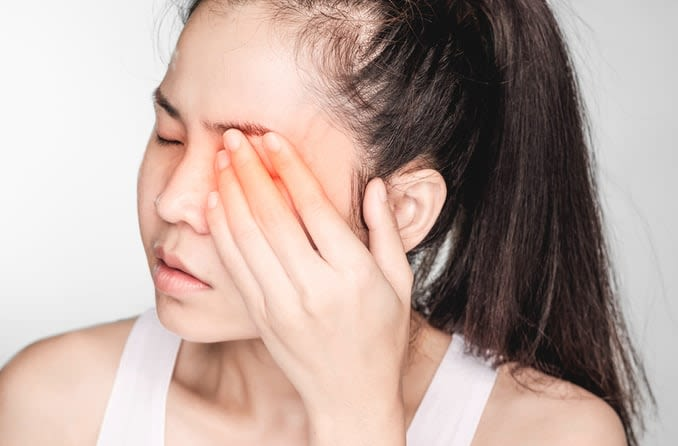 A young woman experiencing eye discomfort gently covers her eye with her hand