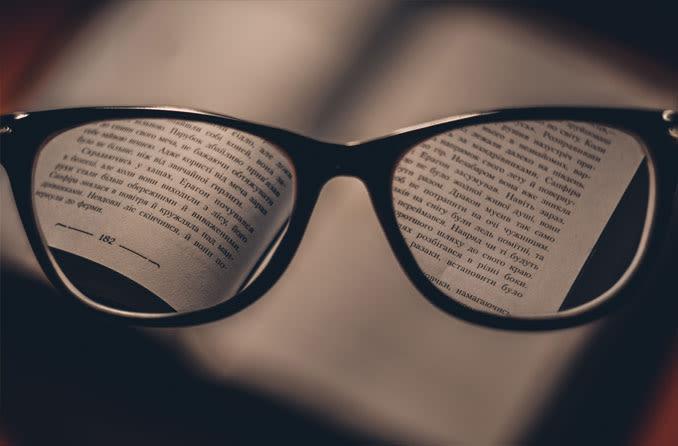 Par de óculos de leitura, olhando para o livro