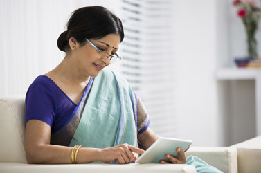 An Indian woman reading on a digital tablet - India