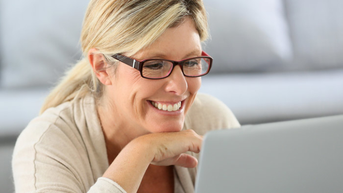Middle aged woman wearing glasses looking at laptop computer