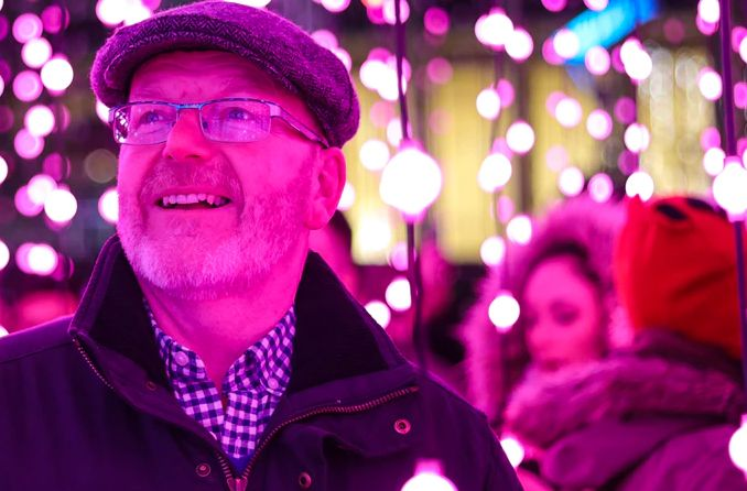 Middle-aged man wearing glasses looking at Christmas lights